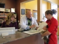 Dr. Corradini helps a client check out at the front desk