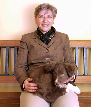 Nicky sits on bench in Bradford Animal Clinic with puppy on her lap